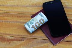 手机、护照和金钱为假期, 100美元背景  免版税库存图片