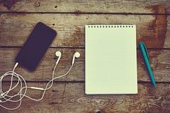 手机、耳机、笔记本和笔在老木桌上 免版税库存图片