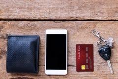 手机和信用卡、钥匙和钱包在棕色木桌上 免版税库存图片