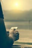 手机在妇女的手上,在日落 免版税库存照片