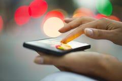 手机在妇女的手,轻的背景城市上 免版税库存照片