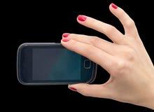 手机在手中有在黑背景的红色指甲油的 库存图片