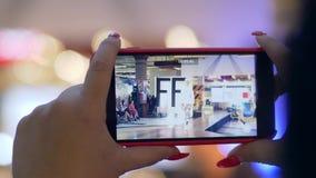 手机在时装,在运动服步行的女性模型拍摄录影在聚光灯的指挥台 股票录像