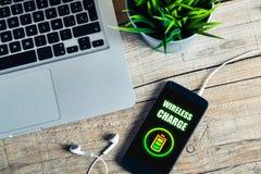手机在有无线充电作用的办公室在屏幕,被安置在办公室 免版税图库摄影