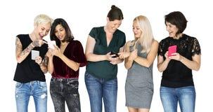 手机微笑和联络的幸福小组女朋友 免版税库存照片
