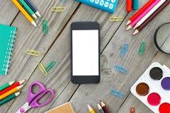 黑手机用在木表上的学校设备 库存图片