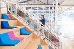 手机的妇女走台阶的在五颜六色的办公室 免版税库存照片