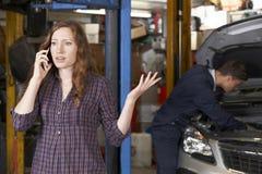手机的沮丧的女性顾客在汽车修理店 免版税库存照片