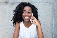 手机的笑的非裔美国人的妇女 免版税图库摄影