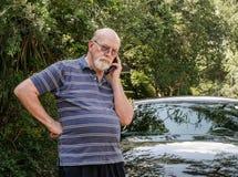 手机的老人在汽车旁边的路要求帮助 免版税库存照片