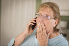 手机的震惊资深妇女在厨房里 免版税库存图片