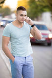 手机的年轻人在城市街道上 免版税库存照片