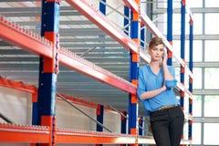 手机的年轻女实业家在仓库里 免版税库存照片