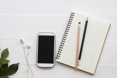 手机,学生研究的文字笔记笔记本  免版税库存图片
