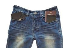 手机,护照书,汽车钥匙,在蓝色牛仔裤口袋旅行的概念的笔记本,裁减路线 免版税库存图片