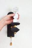 手松开在发光设备的钨电灯泡在白色墙壁上 库存照片