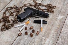 手枪、scatteed弹药筒、香烟、打火机、一把折叠的刀子和一个生锈的链子的布局 免版税库存照片