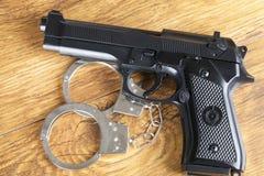 手枪和手铐在木背景 免版税图库摄影