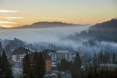 手段村庄在用密集的有薄雾的云杉的森林盖的有雾的蓝色山小山背景的房屋建设在明亮下 图库摄影