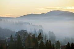 手段村庄在用密集的有薄雾的云杉的森林盖的有雾的蓝色山小山背景的房屋建设在明亮下 免版税库存照片