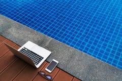 手段的工作场所 膝上型计算机和智能手机玻璃临近蓝色游泳池 现代的小配件 免版税库存图片
