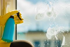 手清洁窗口在家使用洗涤剂旧布 免版税库存图片