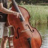 手特写镜头在低音提琴/低音提琴使用户外 免版税库存照片