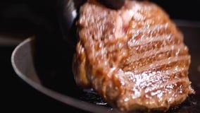 手特写镜头在拿着在煎锅的黑橡胶手套的可口油煎的牛排 股票录像