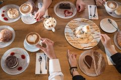 手特写镜头用点心和咖啡杯在咖啡馆 库存照片