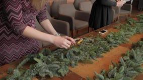 手特写镜头 卖花人在工作:妇女递做圣诞节装饰诗歌选冷杉Nobilis 新年好晚餐 影视素材