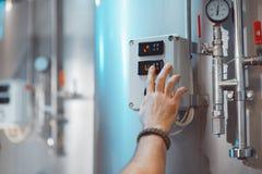 手特写镜头 在啤酒厂的温度传感器设置 库存图片