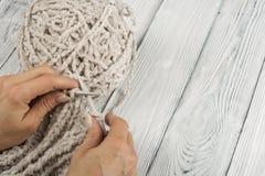 手特写镜头,针编织 羊毛球与轮幅的 对手工制造在木桌上 免版税库存照片