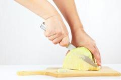 手用在一个木切板的一棵刀子细片圆白菜 库存照片