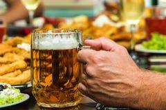 手用在桌上的啤酒用食物 免版税库存照片