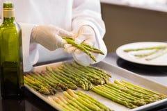 手用新鲜的芦笋和油在厨房里 免版税库存照片