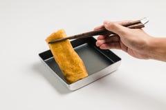 手用筷子夹子卷煎蛋 库存照片