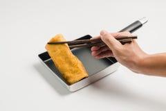 手用筷子夹子卷煎蛋 免版税库存图片