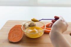 手用蔬菜泥或婴儿食品在匙子 免版税库存照片