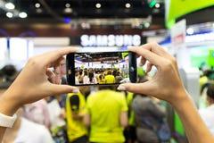 手用途智能手机在泰国流动商展事件的捕获人群 图库摄影