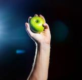 手用绿色苹果,在黑背景,被隔绝,概念 免版税库存图片
