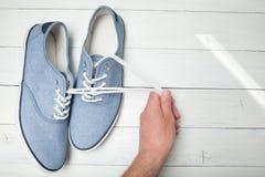 手由在白色木背景的鞋带拉扯软的舒适的蓝色运动鞋 库存图片