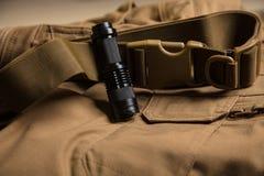 手电和钩子在棕色纺织品 免版税图库摄影