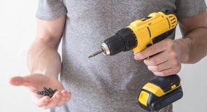 手电工具:一把黄色电螺丝刀在一个人和一个螺丝的手上在棕榈 免版税图库摄影