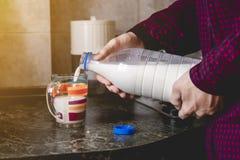 手的关闭倾吐在玻璃的水在被定调子的厨房用桌上 库存照片