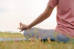 手的关闭和一半身体健康妇女在莲花瑜伽位置坐早晨在公园 实践的瑜伽做凝思 库存照片