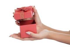手的关闭打开一个红色礼物盒 免版税库存图片