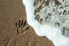 手的印刷品在沙子的 库存图片