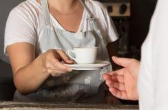 手的女性barista服务咖啡关闭 库存图片
