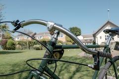 手的特写镜头在一个私有庭院制造了道路被看见的竟赛者自行车 库存图片