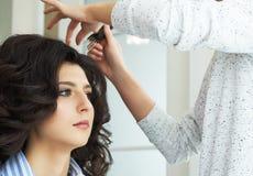 手的特写镜头梳在顾客的发式专家的视图和梳子一种新的发型在发廊朝向 库存照片